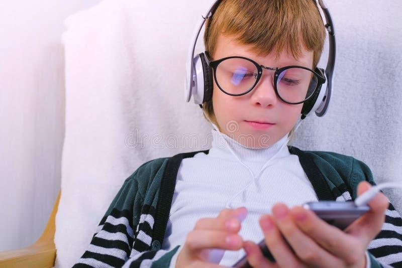 Le garçon introduit un message se reposant dans le fauteuil à la maison dans des écouteurs images stock