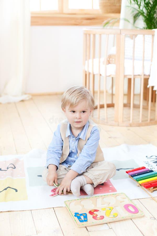 Le garçon joue avec les jouets en bois à la maison Jouets en bois éducatifs pour l'enfant Portrait d'un garçon s'asseyant sur le  photographie stock libre de droits