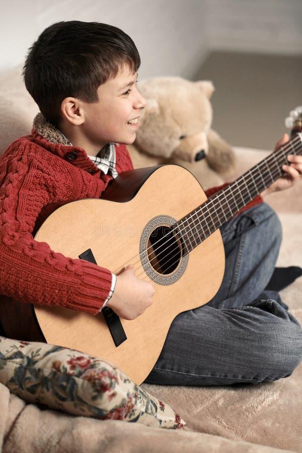 Le garçon joue avec une guitare acoustique, se repose sur le sofa avec un jouet d'ours photos stock