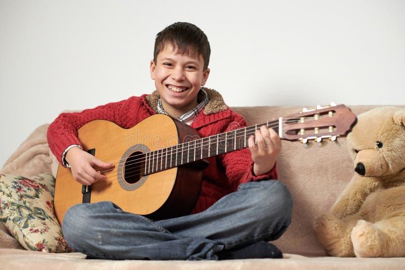 Le garçon joue avec une guitare acoustique, se repose sur le sofa avec un jouet d'ours photo stock