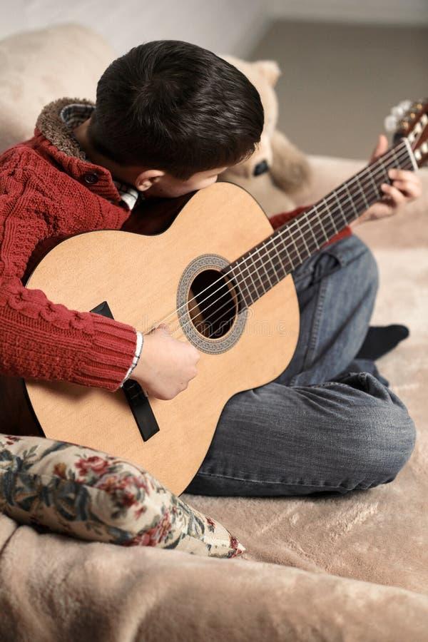 Le garçon joue avec une guitare acoustique, se repose sur le sofa avec un jouet d'ours images libres de droits
