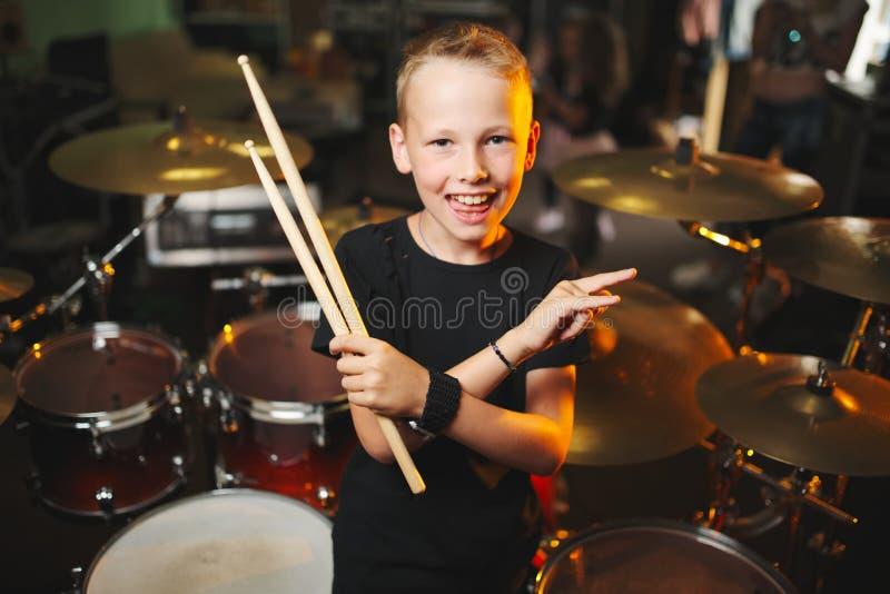 Le garçon joue des tambours dans le studio d'enregistrement photo libre de droits