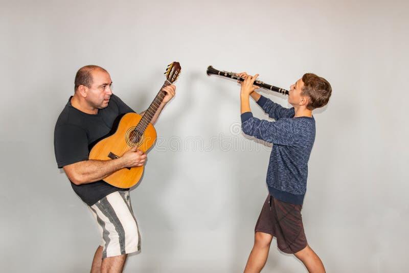 Le garçon joue la guitare et la clarinette dans différentes poses, posant dans le studio photographie stock libre de droits