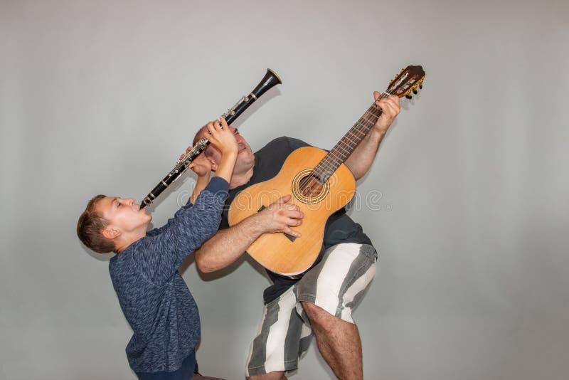 Le garçon joue la guitare et la clarinette dans différentes poses, posant dans le studio images libres de droits