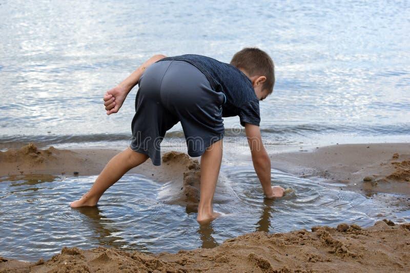 Le garçon joue la saleté sur la berge en été Les vacances des enfants actifs extérieures images stock