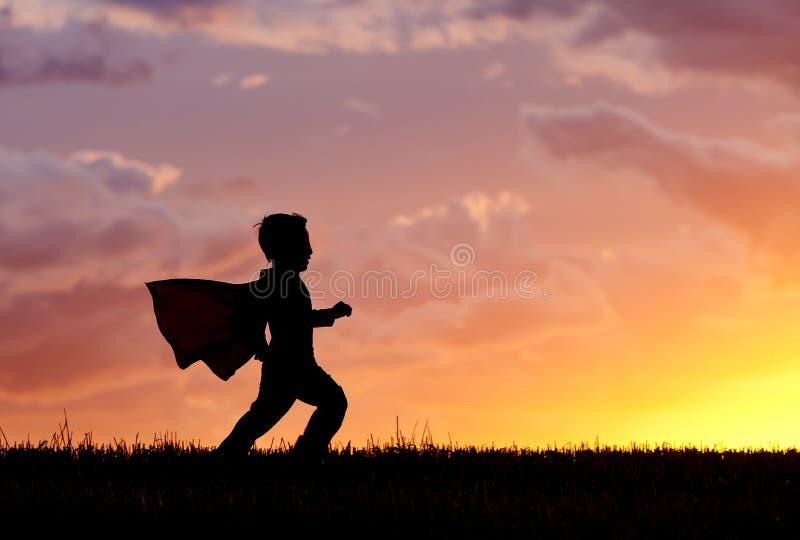 Le garçon joue le héros superbe au coucher du soleil. images stock
