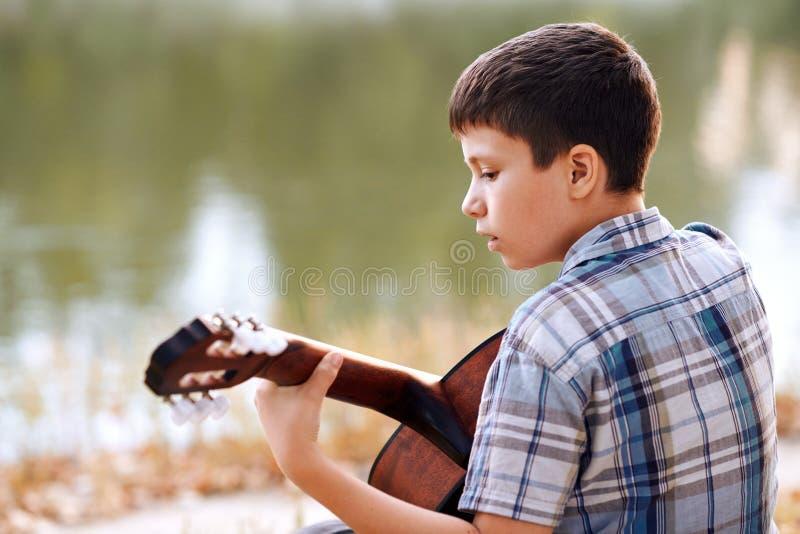 Le garçon joue une guitare acoustique, s'assied sur la banque de la rivière, de la forêt d'automne au coucher du soleil, de la be photo libre de droits
