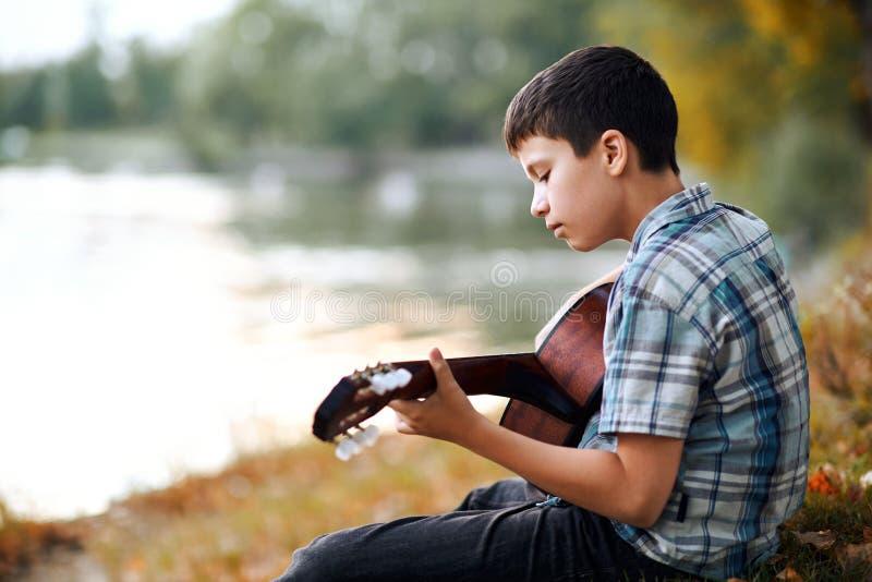 Le garçon joue une guitare acoustique, s'assied sur la banque de la rivière, de la forêt d'automne au coucher du soleil, de la be photos stock