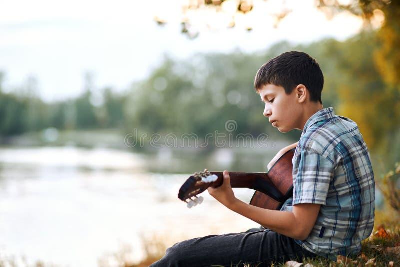 Le garçon joue une guitare acoustique, s'assied sur la banque de la rivière, de la forêt d'automne au coucher du soleil, de la be photos libres de droits