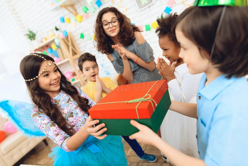 Le garçon joyeux d'anniversaire dans le chapeau de fête reçoit le cadeau de la petite fille dans l'image de la princesse photos libres de droits
