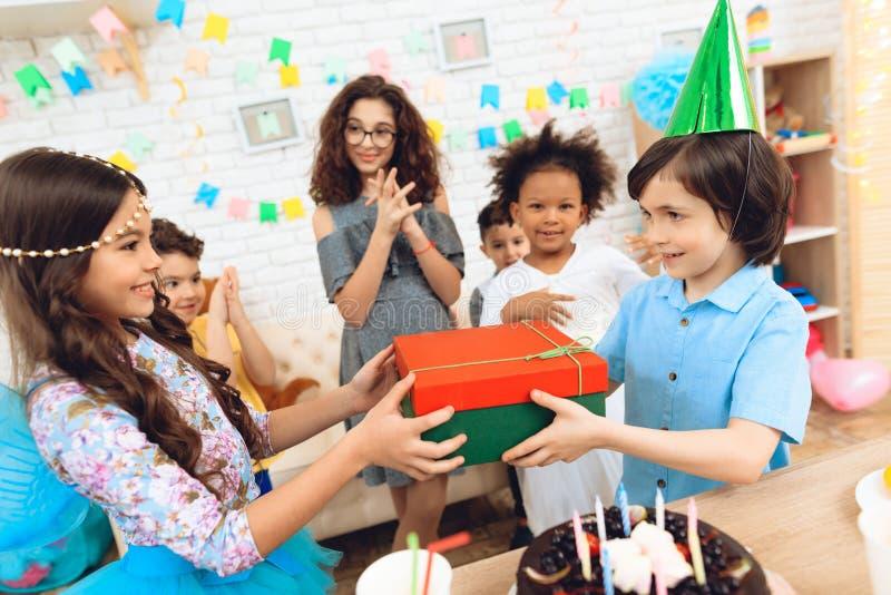 Le garçon joyeux d'anniversaire dans le chapeau de fête reçoit le cadeau de la petite fille dans l'image de la princesse photographie stock