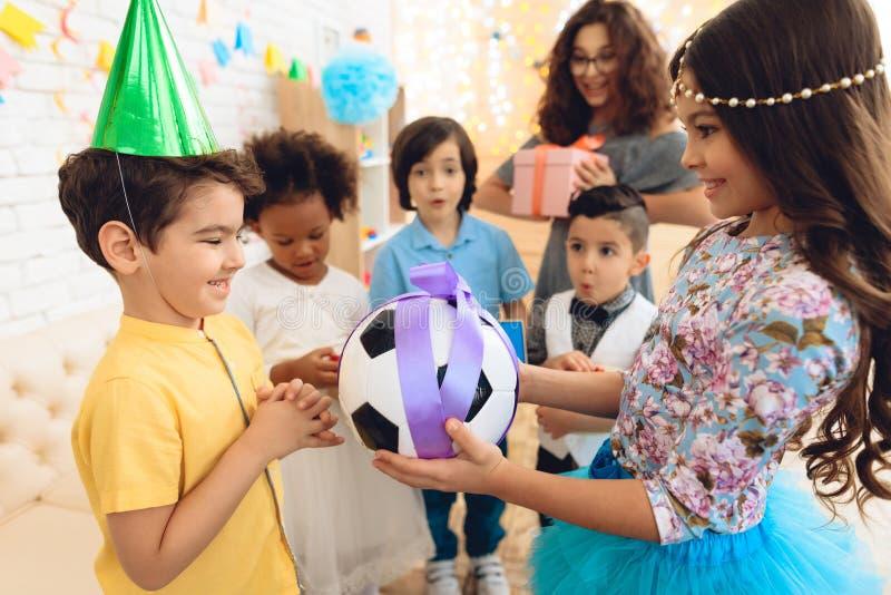 Le garçon joyeux d'anniversaire reçoit la boule du football comme cadeau d'anniversaire Partie de joyeux anniversaire photo libre de droits