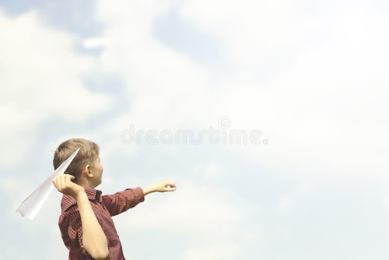 Le garçon a l'amusement dans des avions de papier de lancement dans le ciel photo stock