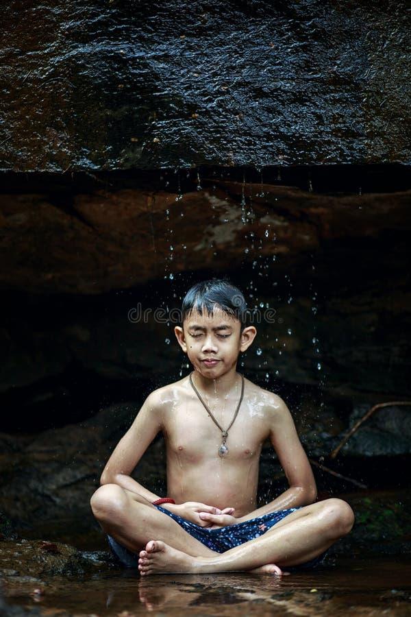 Le garçon méditant sous une cascade bascule dans les bois quelque part photos stock