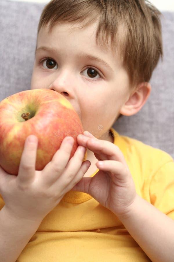 Le garçon mange la grande pomme rouge photos stock