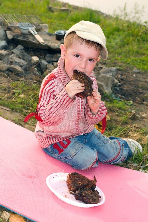 Le garçon mange le barbecue photographie stock