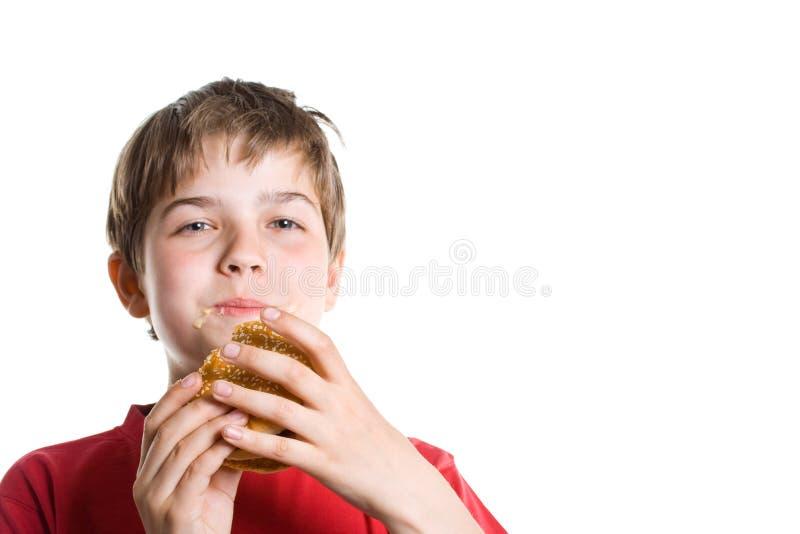 Le garçon mangeant un hamburger. photo libre de droits