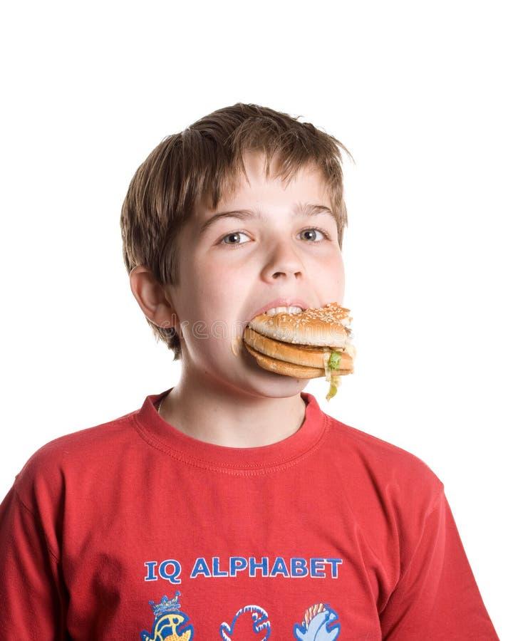 Le garçon mangeant un hamburger. photo stock