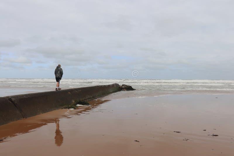 Le garçon marche à l'océan chez Omaha Beach photographie stock