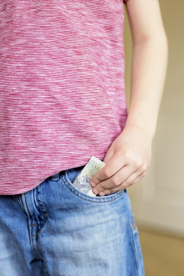 Le garçon met le billet de banque d'argent liquide dans la poche photo libre de droits