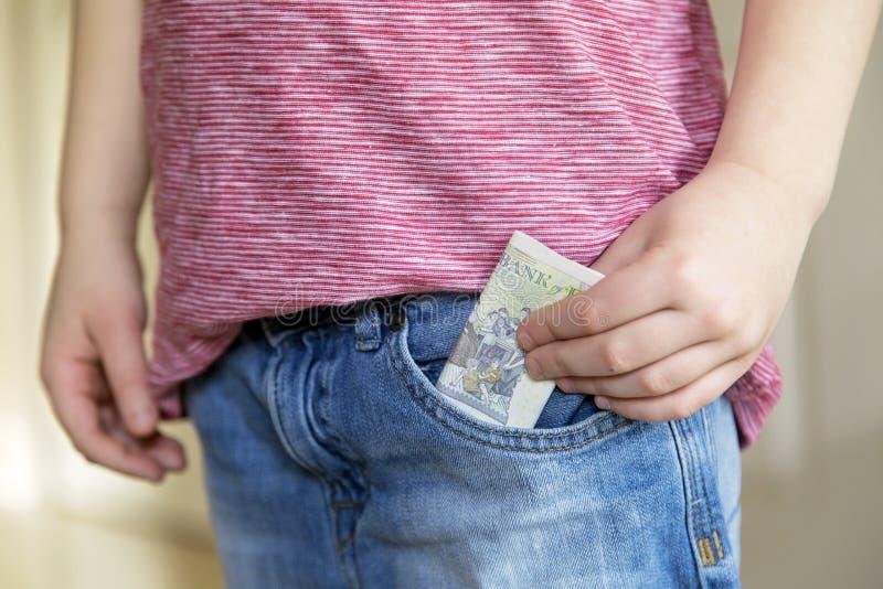 Le garçon met le billet de banque d'argent liquide dans la poche image libre de droits