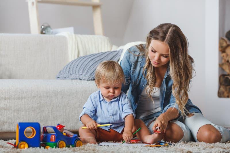 Le garçon mignon de mère et d'enfant jouent ensemble à l'intérieur à la maison image libre de droits