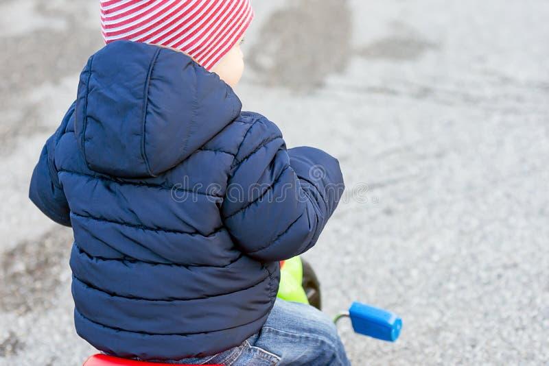 Le garçon mignon de petit enfant dans des vêtements automnaux chauds a tourné par derrière avoir l'amusement avec le tricycle images libres de droits