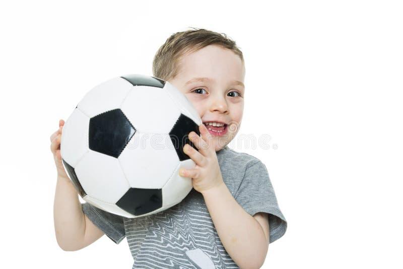 Le garçon mignon juge une boule du football d'isolement sur le fond blanc Le football photo libre de droits