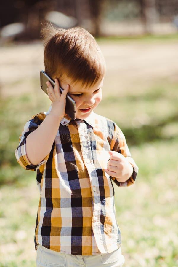 Le garçon mignon parle par le téléphone portable en parc image libre de droits