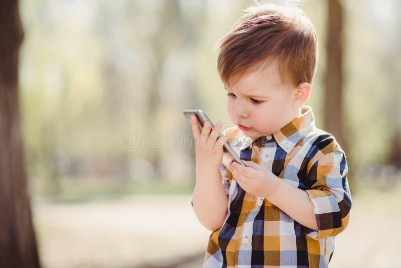 Le garçon mignon parle par le téléphone portable en parc images libres de droits