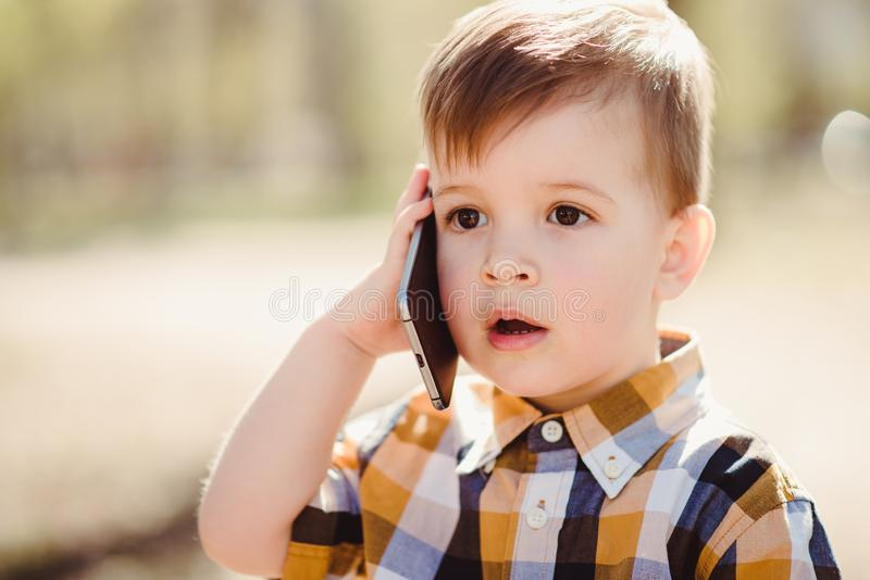 Le garçon mignon parle par le téléphone portable en parc photographie stock libre de droits