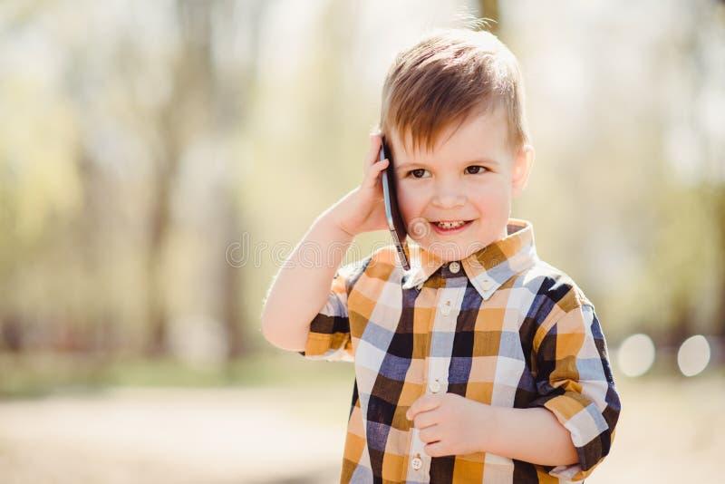 Le garçon mignon parle par le téléphone portable en parc images stock