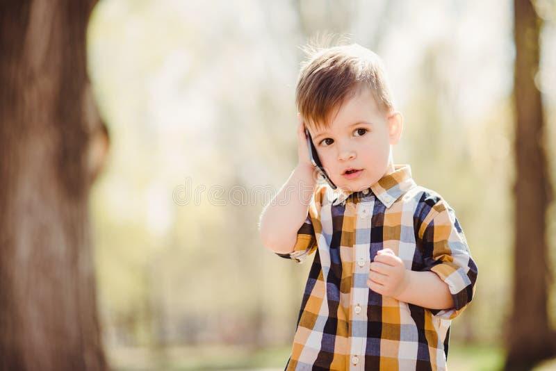 Le garçon mignon parle par le téléphone portable en parc photo stock