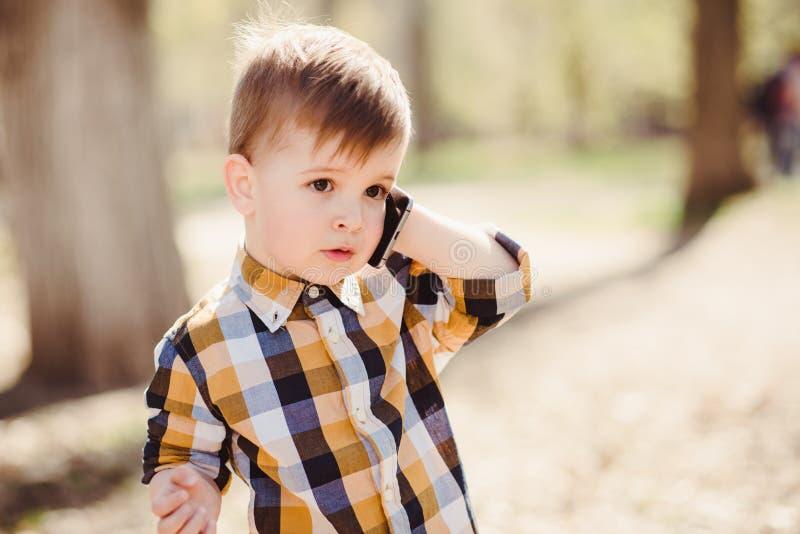 Le garçon mignon parle par le téléphone portable en parc image stock
