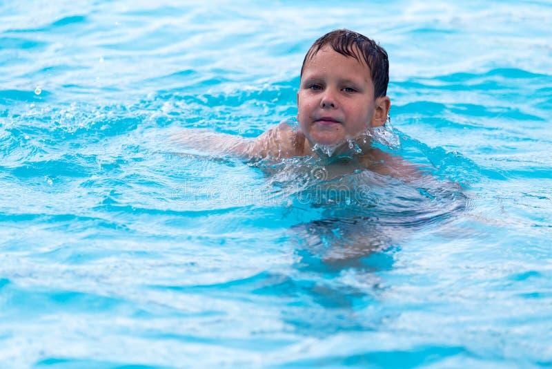 Le garçon nage dans la piscine image stock