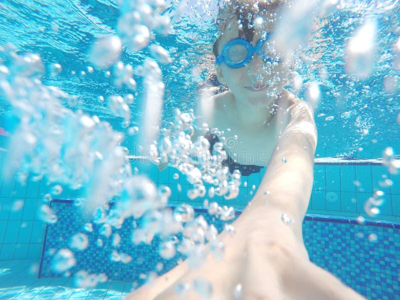 Le garçon nage sous l'eau dans la piscine photos stock