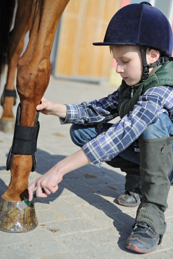Le garçon nettoie un sabot de cheval photographie stock