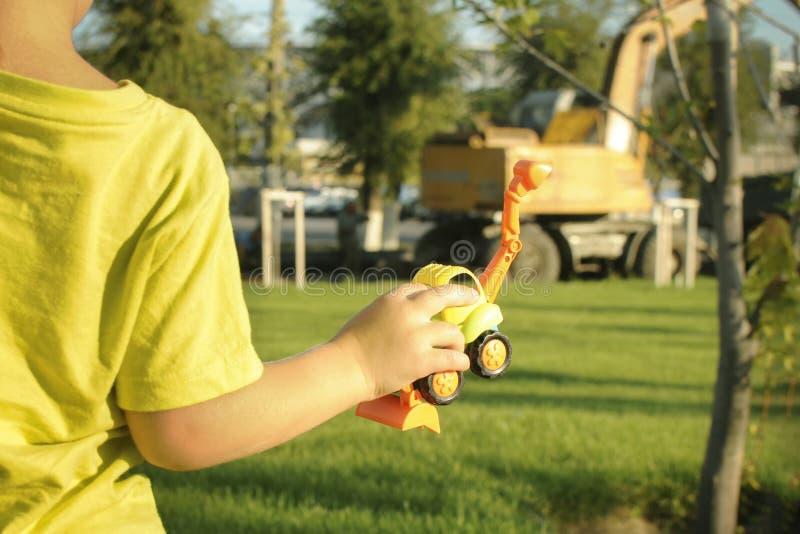 Le garçon observe le travail de l'excavatrice, tient une excavatrice de jouet dans sa main image libre de droits