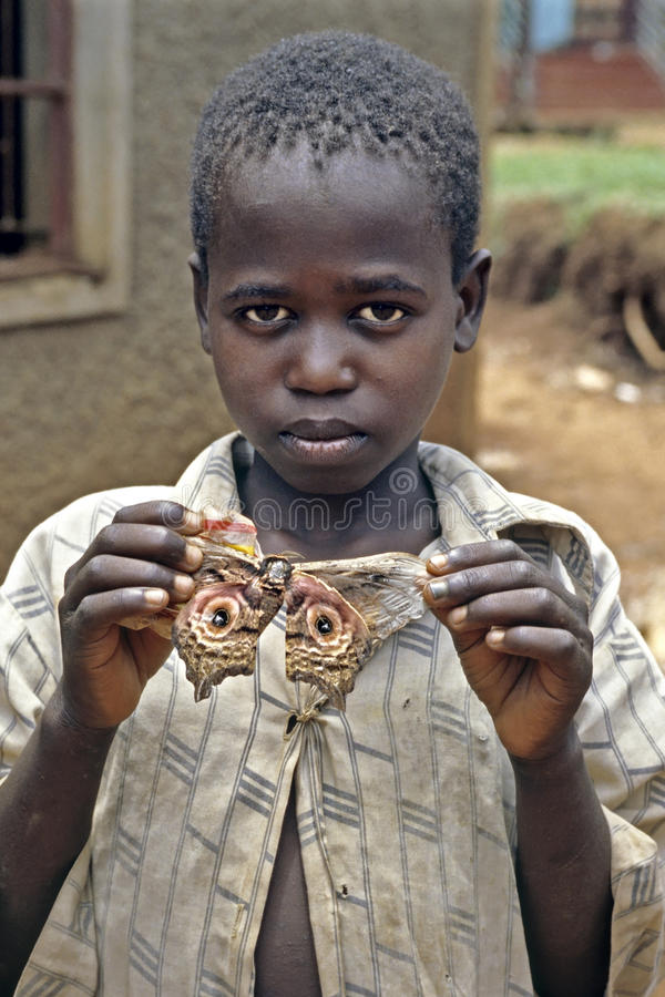 Le garçon ougandais pose fièrement avec la mite colorée photo libre de droits