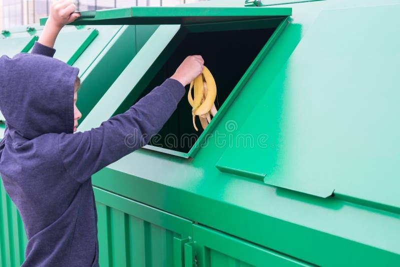 Le garçon ouvre le réservoir de déchets et jette une peau de banane photographie stock libre de droits
