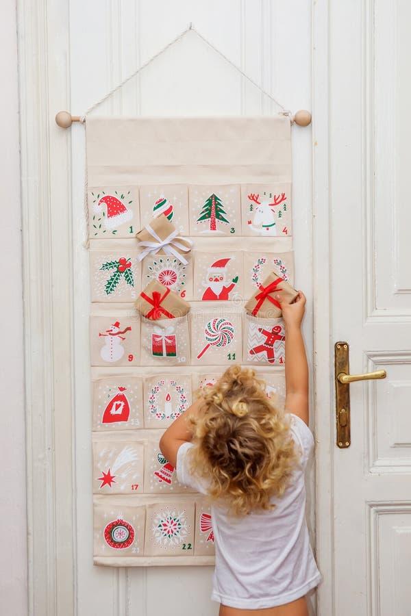 Le garçon ouvre un cadeau du calendrier de l'avènement photos stock