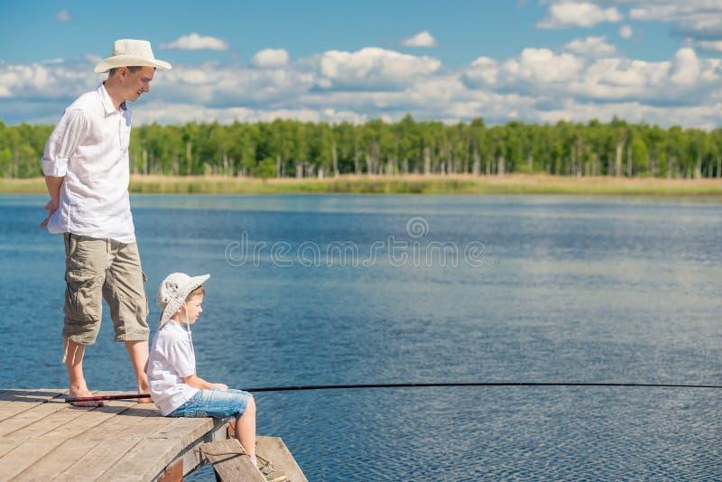 Le garçon pêche sur le pilier avec une canne à pêche sous le supe image libre de droits