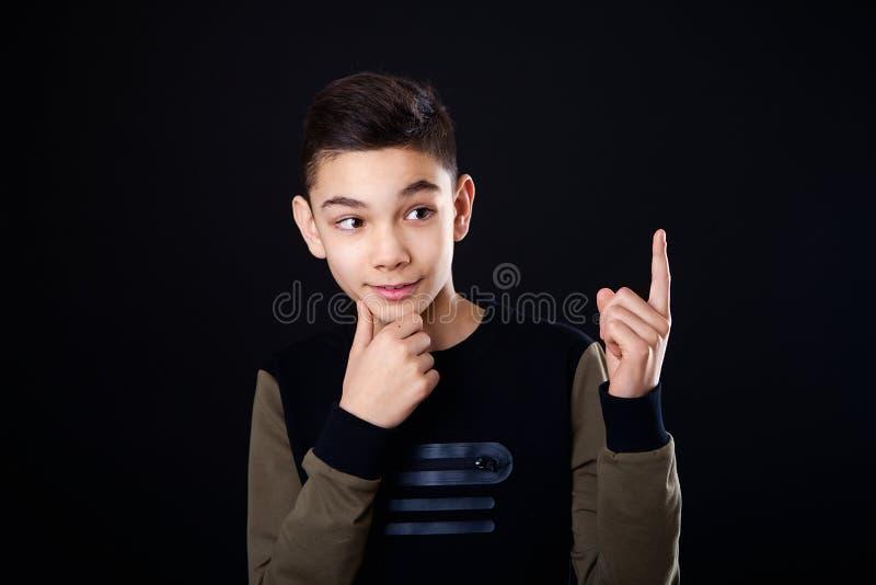 Le garçon pense pensées Le type montre un doigt, une idée Place pour le texte Fond noir, studio, d'isolement photographie stock