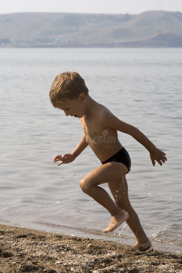 le garçon peu à l'extérieur exécute l'eau photos stock