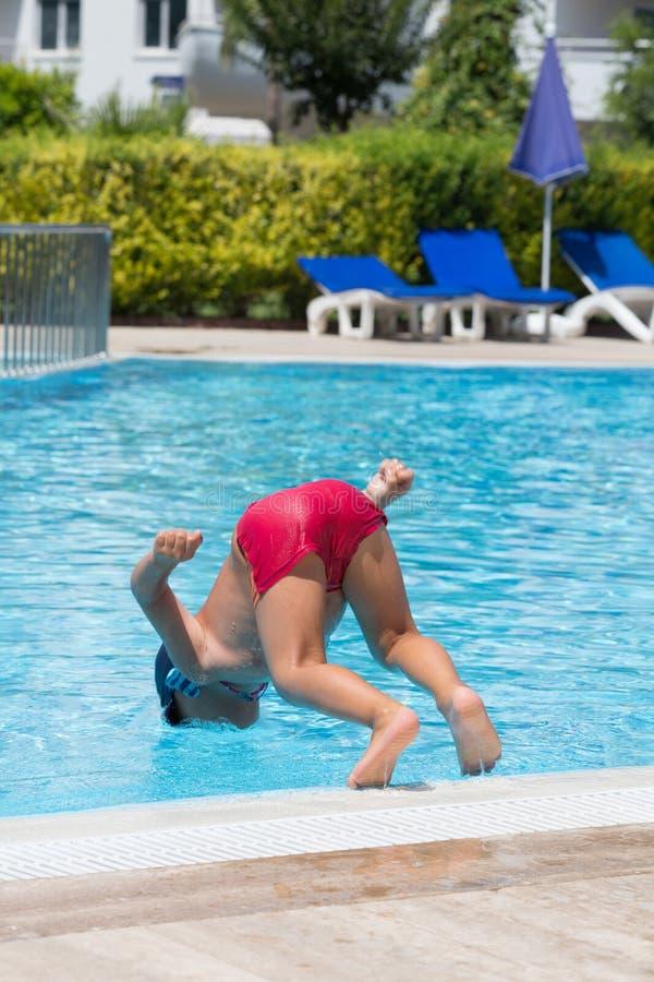 Le garçon plonge dans la piscine. photos libres de droits
