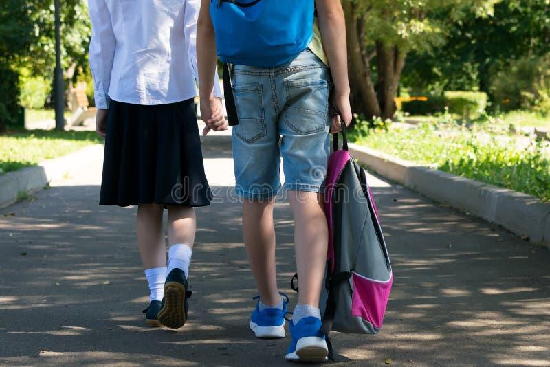 Le garçon porte le sac à dos de la fille sur le chemin de la maison de l'école par le parc photographie stock libre de droits