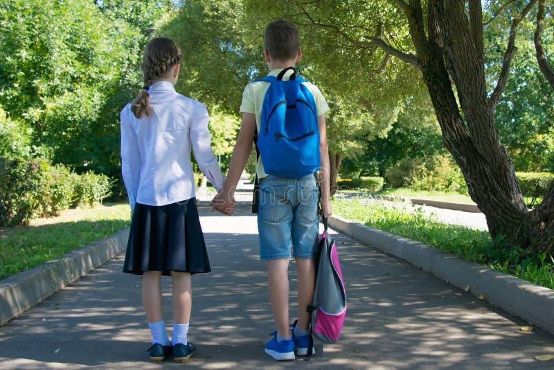Le garçon porte le sac à dos du ` s de fille sur le chemin à la maison photos stock