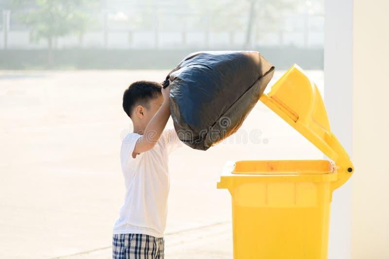 Le garçon portent des déchets photo libre de droits