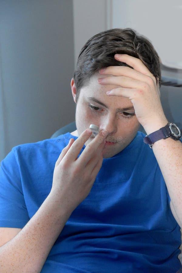 Le garçon prend sa température avec un thermomètre clinique images stock