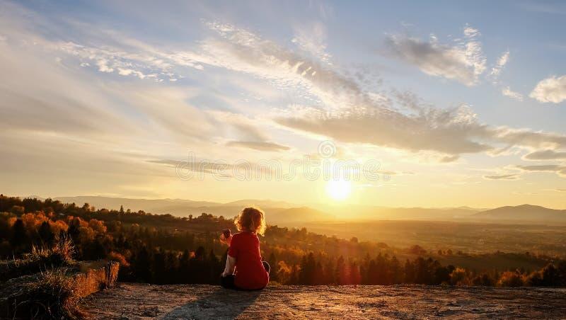Le garçon profite du coucher de soleil dans les montagnes image stock